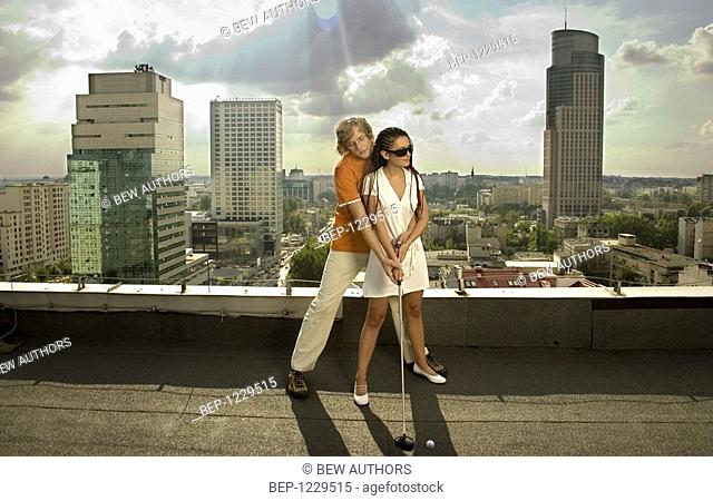 Couple playing golf on the roof