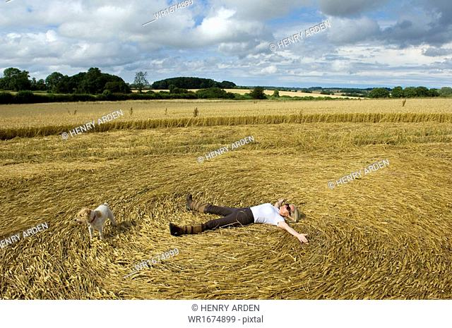 A farmer lying down on his back in the stubble of a freshly cut crop field with arms and legs spread out, creating a pattern in the straw