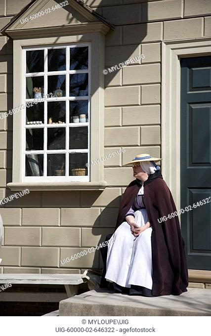 A woman sits outside a shop on the main street through Colonial Williamsburg, Virginia