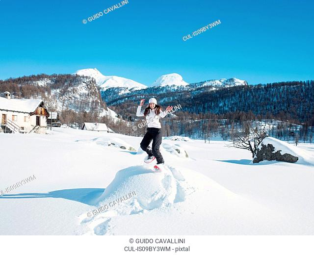 Young woman in knit hat jumping in snow covered landscape, portrait, Alpe Ciamporino, Piemonte, Italy