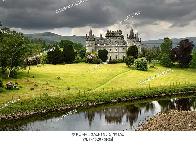 Inveraray Castle reflected in the River Aray at Loch Fyne with dark clouds and golden grass in the Scottish Highlands Scotland UK
