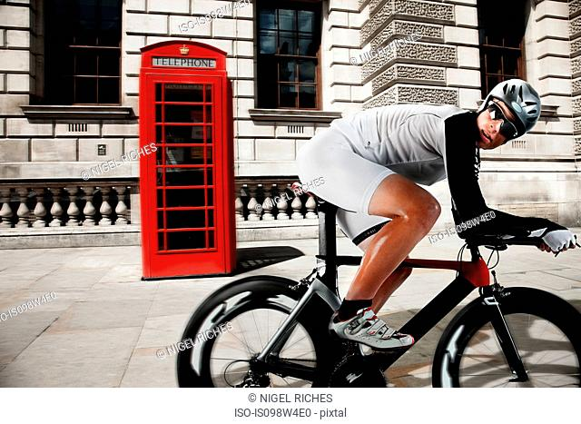Cyclist cycling past red telephone box