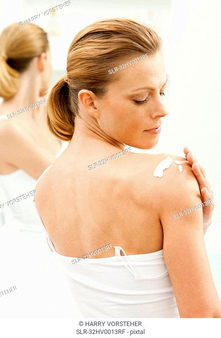 Woman moisturizing her shoulders