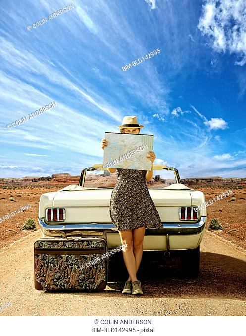 Caucasian woman with convertible reading map on remote road