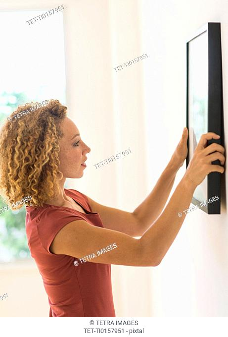 Young woman hanging print on wall