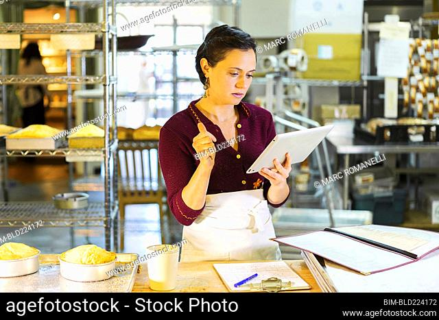 Caucasian woman using digital tablet in bakery