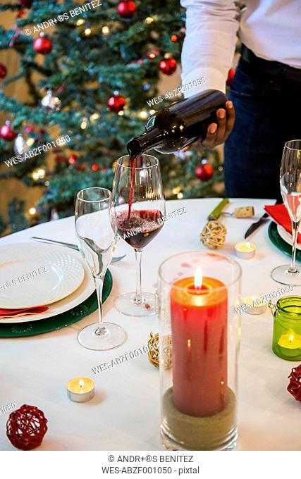 Man serving wine at Christmas dinner
