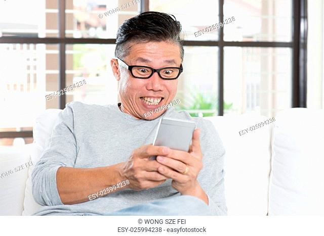 Portrait of happy 50s mature Asian man using smart phone with excited face expression, sitting on sofa at home