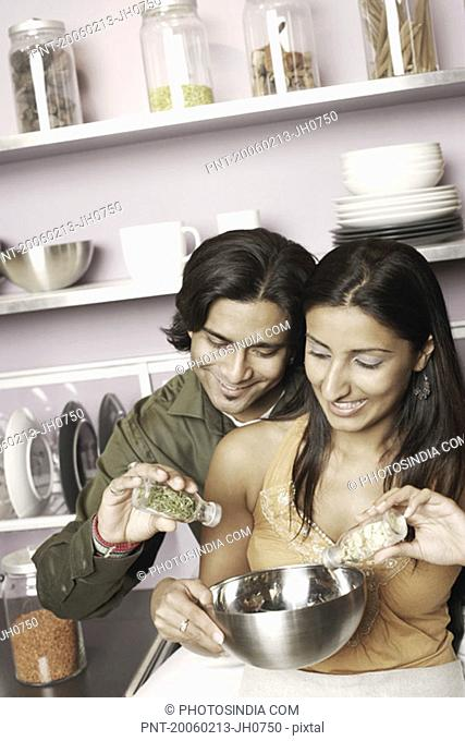 Young couple pouring herbs in a bowl