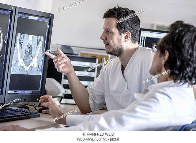 Two doctors discussing x-ray image on computer screen