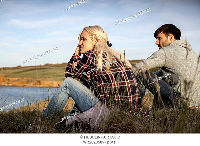 Young couple on water's edge day dreaming