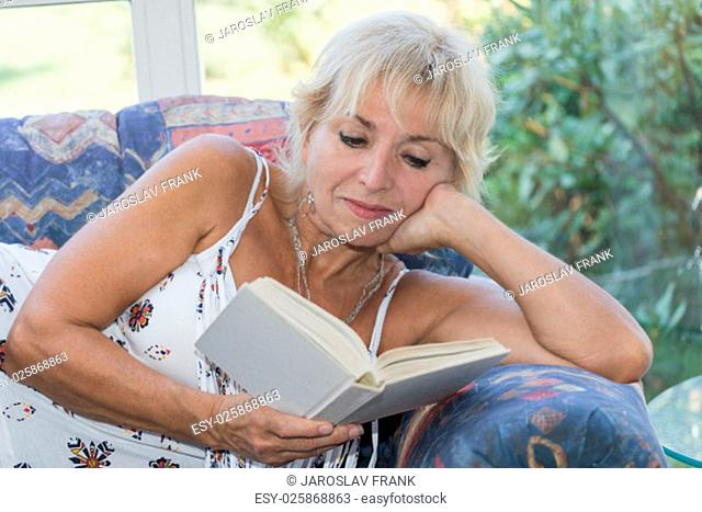 Senior mature blond woman is lying on the couch and reading a book. She looking at the book. All potential trademarks are removed