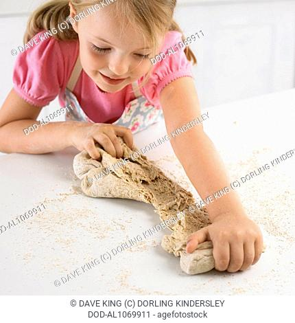 Girl tearing bread dough