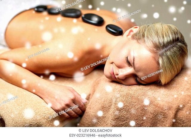 people, beauty, spa, winter and relaxation concept - close up of beautiful young woman having hot stone back massage in spa salon with snow effect