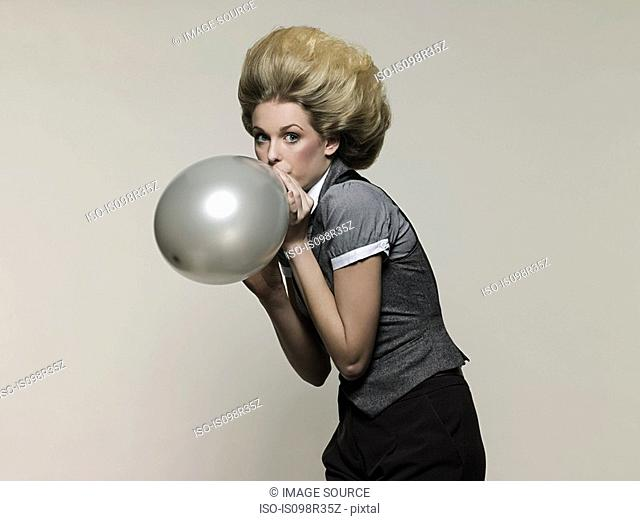 Businesswoman blowing balloon