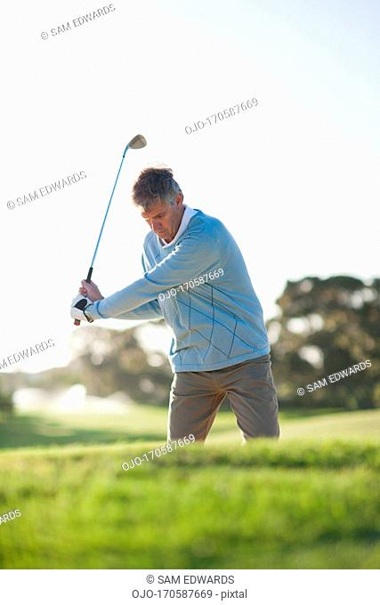 Man playing golf in sand trap