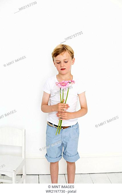 Young boy posing for a picture in a photographers studio, holding a bunch of flowers