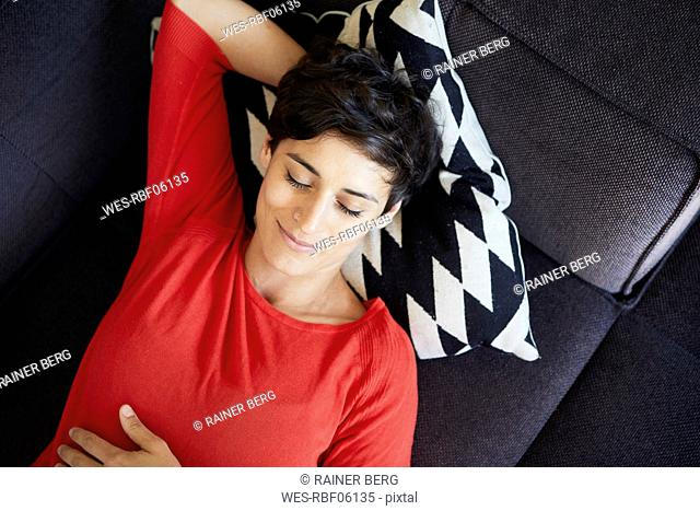 Smiling woman lying on couch at home with closed eyes
