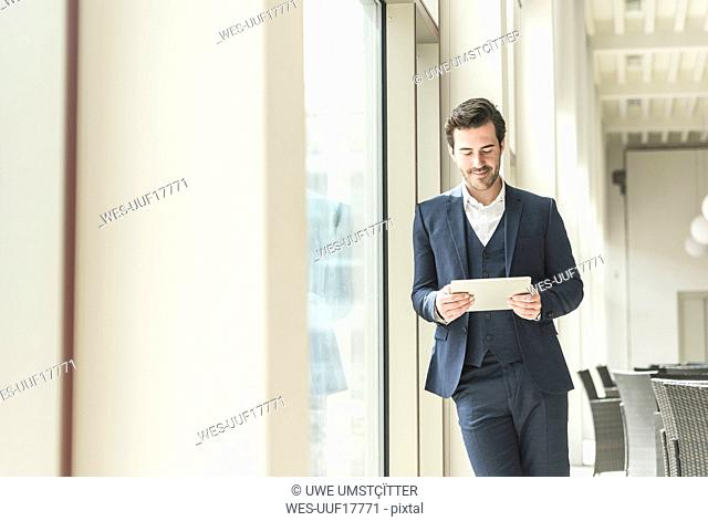 Young businessman standing in office building, using digital tablet, leaning on window