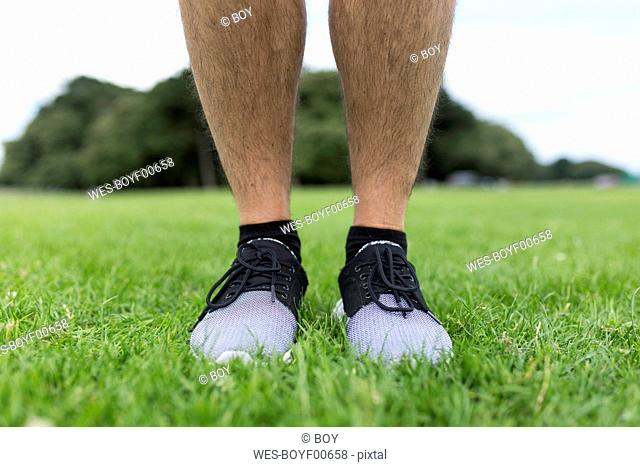 Legs of athlete standing in grass