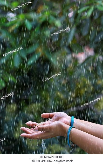 Woman hand with bangles enjoying rain in outdoor