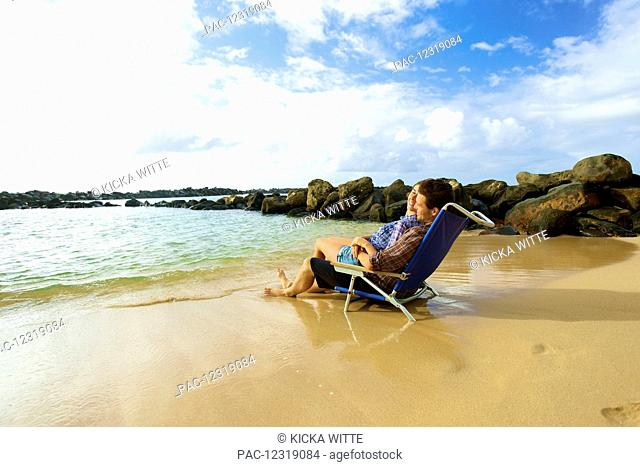 A couple sits in a beach chair together facing the ocean on Lydgate Beach; Kauai, Hawaii, United States of America