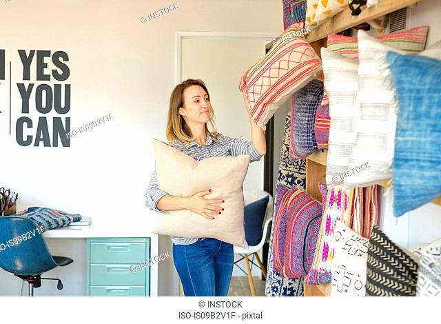 Female textile designer placing cushions on retail studio shelves
