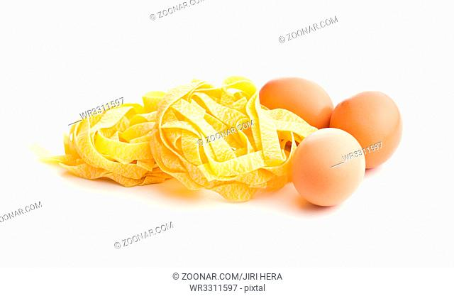 Raw tagliatelle pasta and three eggs isolated on white background