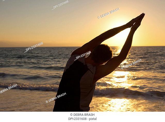 A senior man does yoga on the beach as the sun sets;Puerto vallarta mexico