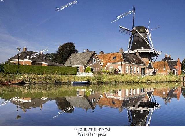 The Hunsingo windmill along the Boterdiep canal in the Dutch village Onderdendam