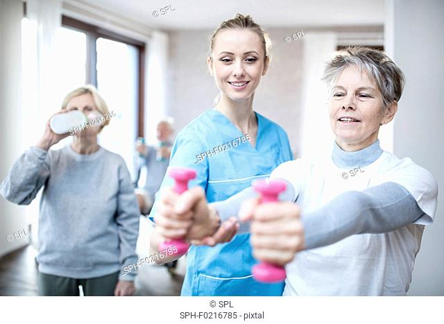 Woman holding hand weights with physiotherapist