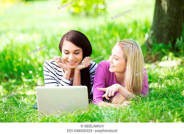 Nice looking young women outdoors. Women using laptop. Beautiful green park as a background