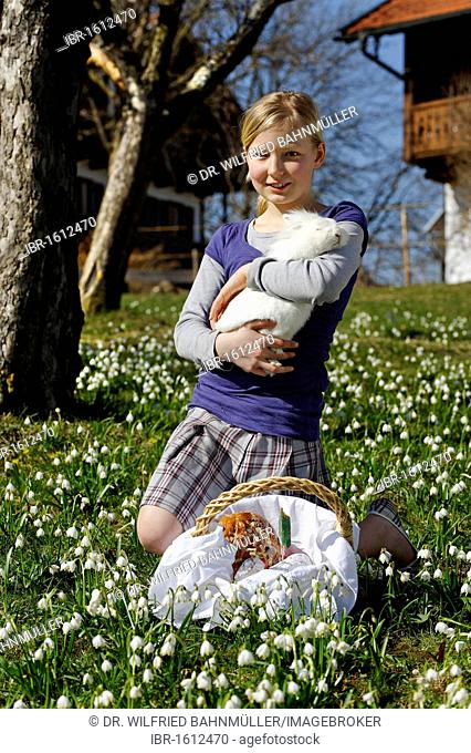 Girl holding a rabbit in her arms, with an Easter basket, Easter bunny