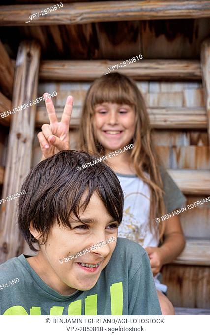 happy young girl showing V sign behind had of her laughing friend