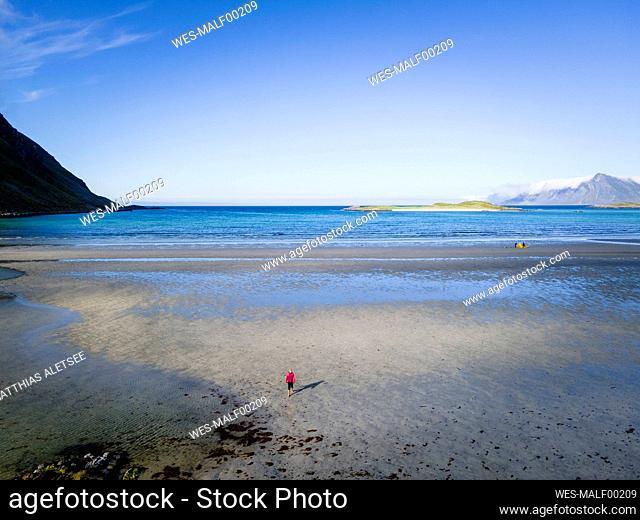 Woman standing on beach at Fredvang, Lofoten, Norway