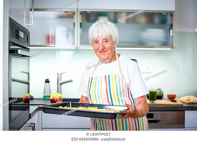 Senior woman cooking in the kitchen - eating and cooking healthy for her family; putting some potates in the oven, enjoying active retirement (shallow DOF;...