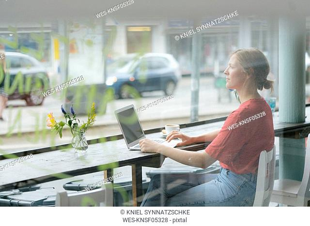 Young woman with cup of coffee and laptop sitting at the window in a cafe
