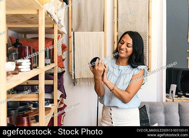 Smiling woman looks at pricing on black cup in luxury home decor store