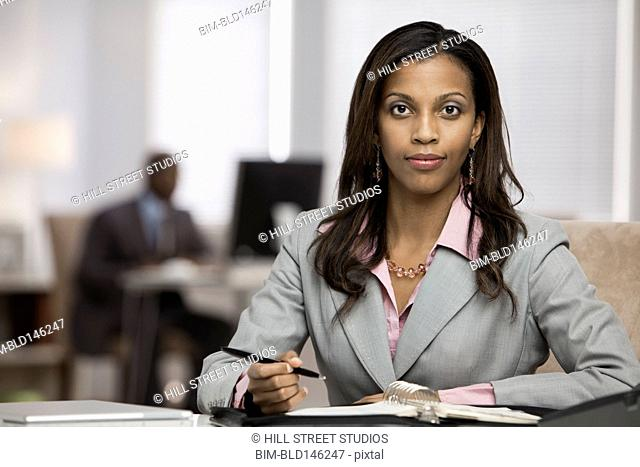 Mixed race businesswoman checking schedule at desk