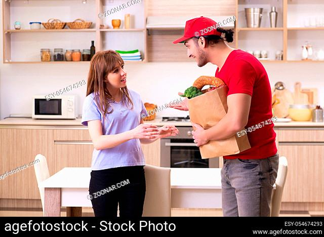 The young male courier in food delivery concept