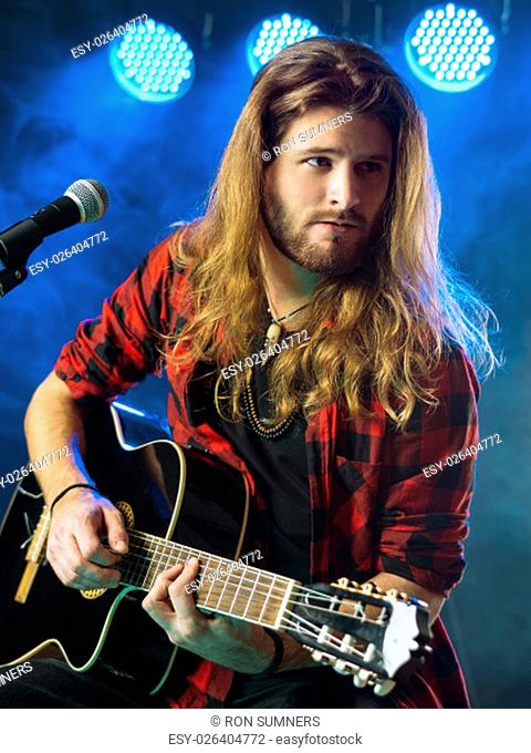 Photo of a young man with long hair and a beard playing an acoustic guitar on stage with lights and concert atmosphere