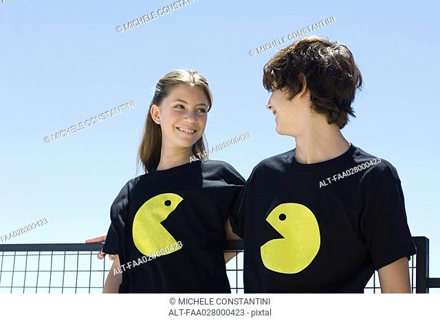 Young couple wearing tee-shirts printed with graphic characters, smiling at each other