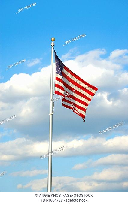 A slightly worn or tattered American flag  A cloudy blue sky is in the background