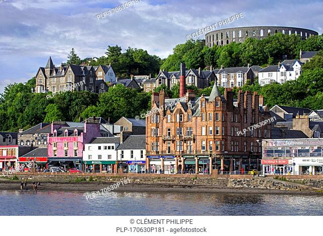 Shops and McCaig's Tower on Battery Hill overlooking the city Oban, Argyll and Bute, Scotland, UK
