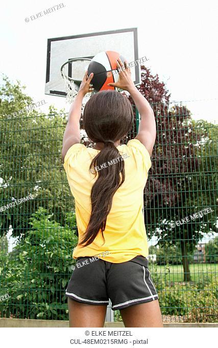 Woman shooting basketball on court