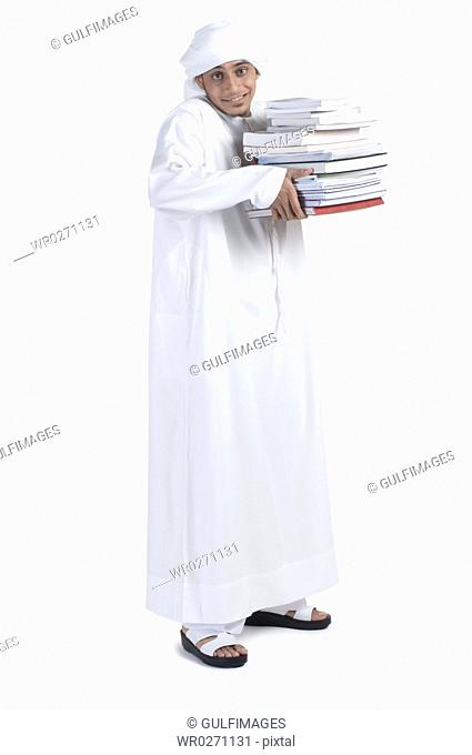 Young man carrying pile of books, portrait