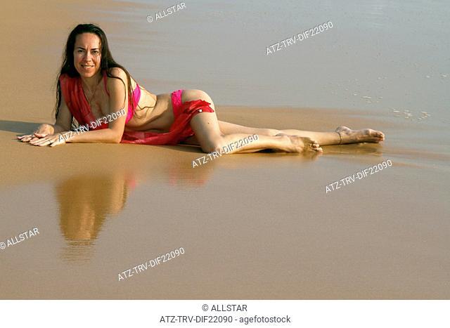 WOMAN RELAXES ON BEACH; BENTOTA, SRI LANKA; 13/03/2013