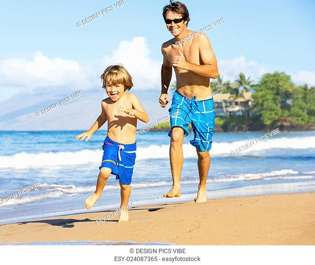 Happy father and son playing and running together at beach, carefree happy fun smiling lifestyle