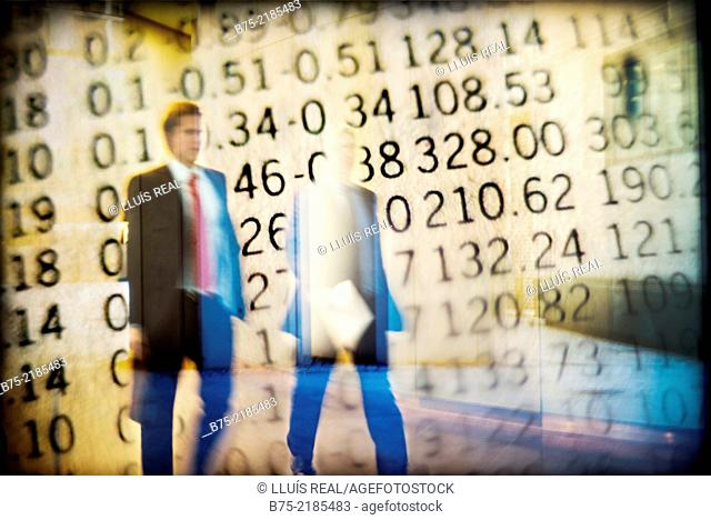 Two unrecognizable businessmen with portfolio walking on top of stock exchange values