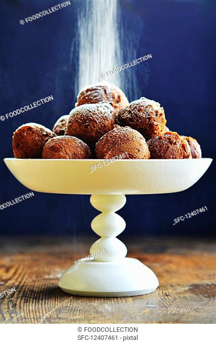 Icing sugar being dusted over doughnuts on an étagère